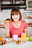 Beautiful woman holds sweet bun with fruits — Stock Photo