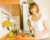 Home life: woman preparing something to eat — Stock Photo
