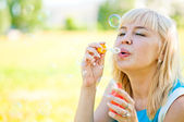 Woman blowing bubbles in park — Stock Photo