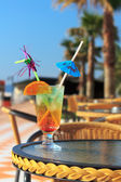 Colorful cocktail with umbrella and slice of orange — Stock Photo