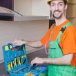 Repairman assembling the furniture at kitchen - Foto Stock