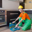 Repairman assembling the furniture at kitchen - 