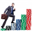 Businessman climbing stacks of casino chips — Stock Photo #11077960