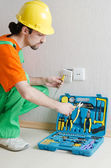 Electrician repairman working in the house — Stockfoto