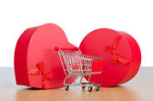 Giftbox and shopping cart on white — Stock Photo