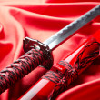 Foto de Stock  : Japanese sword takanon red satin background