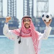 Arab with footbal at seaside - Stock Photo