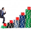 Businessman climbing stacks of casino chips — Stock Photo