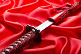 Japans zwaard takana op rode satijnen achtergrond — Stockfoto
