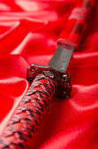 Japanese sword takana on red satin background — Stock Photo