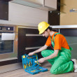 Repairman assembling the furniture at kitchen — Stock Photo