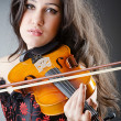 Female violin player against background — Stockfoto