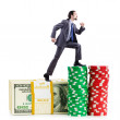 Stacks of casino chips and climbing businessman — Stock Photo