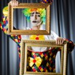Clown with picture frames in studio - Zdjęcie stockowe
