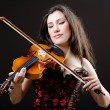 Female violin player against background - Foto Stock