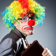 Businessman with clown wig and face paint - Stock Photo