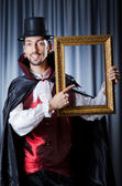 Magician with photoframe in studio — Stock Photo