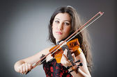 Female violin player against background — Stock Photo
