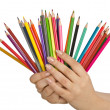 Stock Photo: Hand holding colour pencils on white