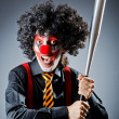 Funny clown with bat in studio — Stock Photo #12152626