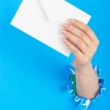 Hand holding paper envelope from hole — Stock Photo