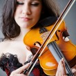 Stock Photo: Female violin player against background