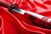 Japanese sword takana on red satin background — Stock Photo