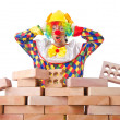 Stock Photo: Bad construction concept with clown laying bricks
