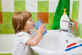Little girl rinses a mouth after toothbrushing. — Stock Photo