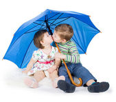 Children sit under a blue umbrella — Stock Photo
