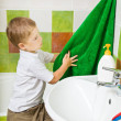 Boy wipes hands a terry towel after washing — Stock Photo