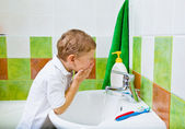 Boy washes the face — Stock Photo