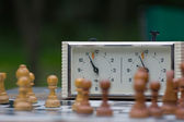 Chessmen stand on a chessboard. Focus on a chess clock — Stock Photo