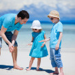 Father and kids at beach - Stock Photo