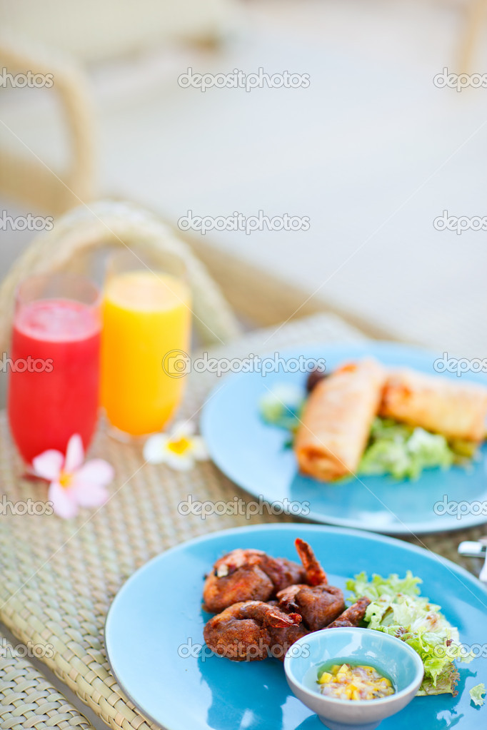 Two plates of delicious asian dishes and two glasses of fresh juices — Stock Photo #11079280