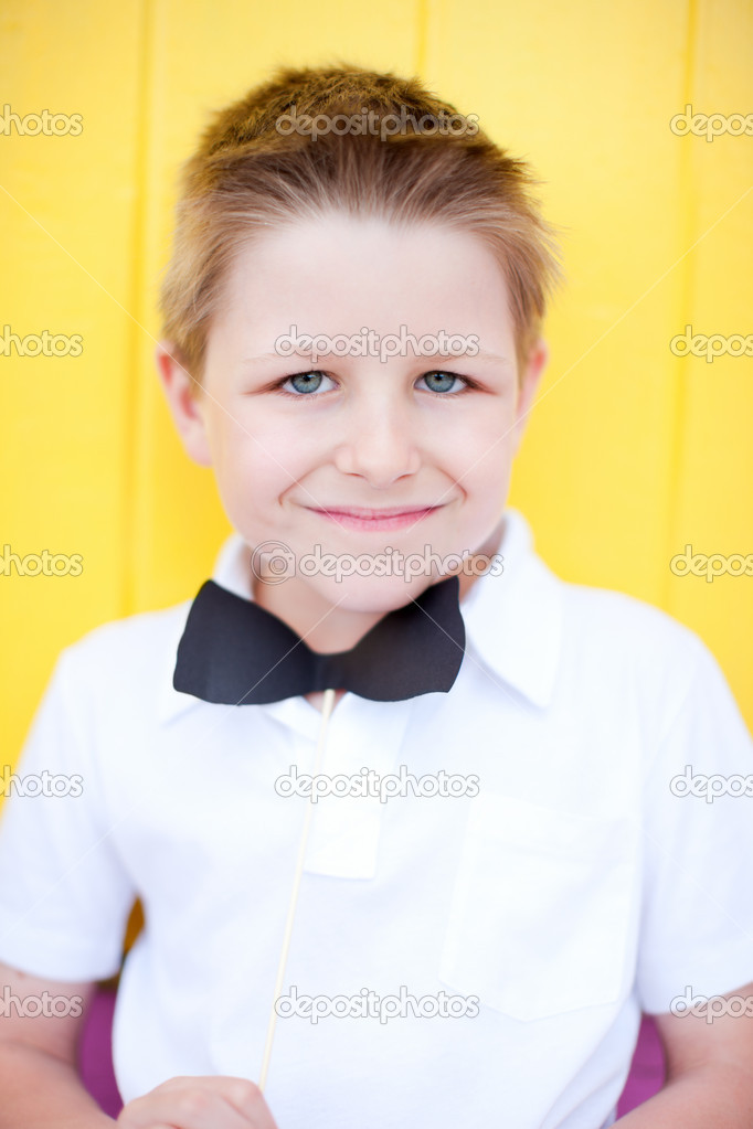Cute boy with bow tie party accessory with colorful wall on background — Stock Photo #11192645