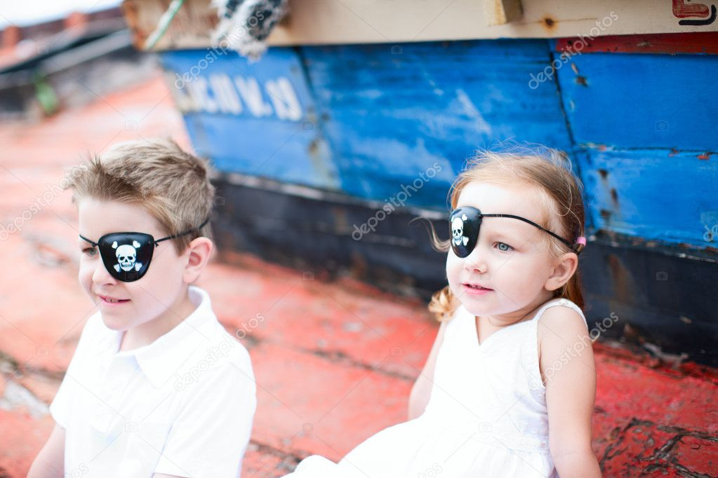 Cute little pirates boy and girl sitting at old boat — Stock Photo #11277381