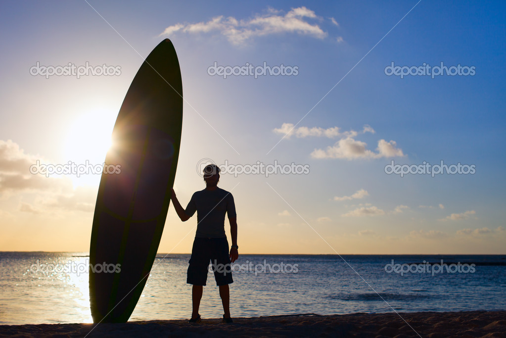 Silhouette of man holding paddle board on a beach at sunset — Stock Photo #12209415