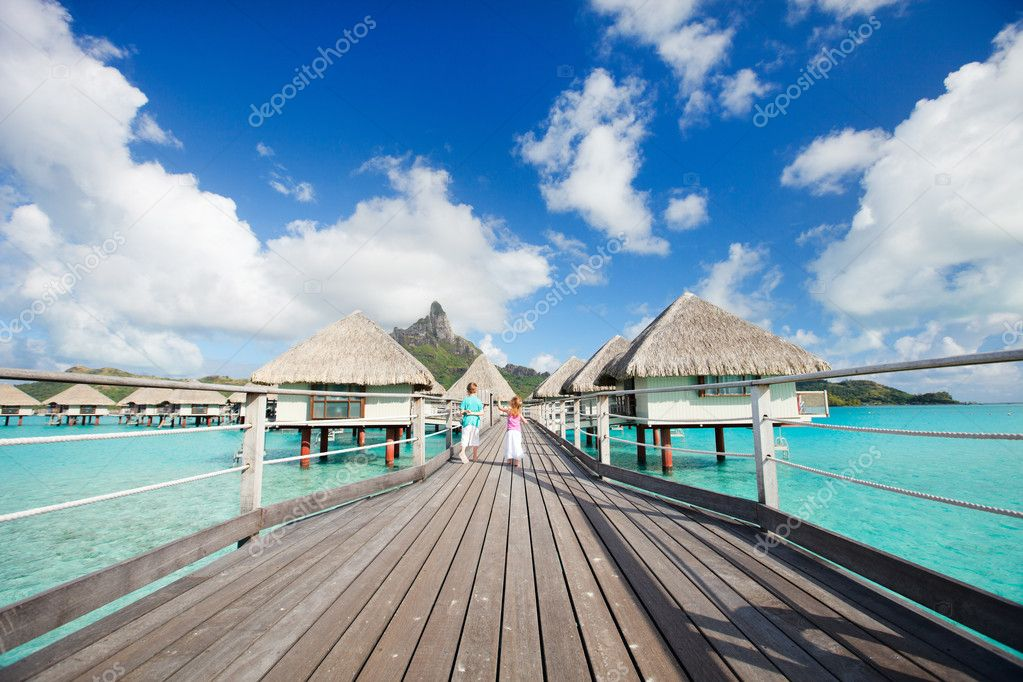 Two kids walking towards over the water bungalowas — Stockfoto #12394125