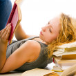 A girl reads a book resting head on pile of books — Stock Photo