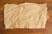 Old paper on wood background. — Stock Photo