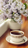 Ceramic cup with coffee and bouquet of lilac — Stock Photo
