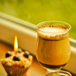 Сoffee latte and a lit candle at rainy window - Stock Photo