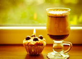 Сoffee latte and a lit candle at rainy window — Stock Photo