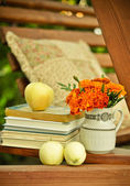 Books, fresh apples, and marigolds in a vase stock image — Stock Photo