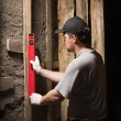Builder measures the level of the wall — Stock Photo