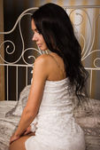 Привлекательная брюнетка, сидя на кровати — Стоковое фото