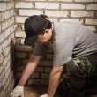 Builder setting tile on cement floor. — Stock Photo