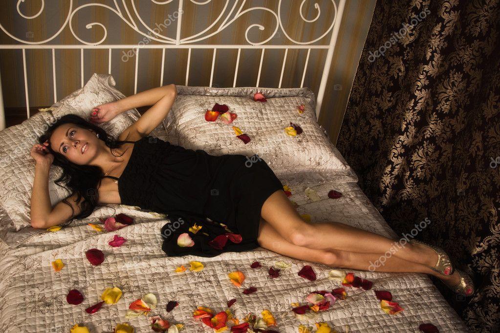 брюнетка лёжа на кровати фото