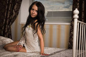 Attractive brunette sitting on the bed — Stock Photo